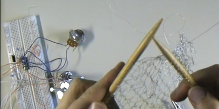 Image of the artists hands knitting silver wire with electronic components visible.